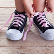 Child hands tie up shoe laces - Stockfoto