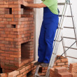 Foto Stock: Worker building masonry heater
