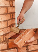 Mason hands with brick — Stock Photo