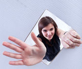 Young girl waving through a hole in cardboard surface — Stock Photo
