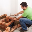 Stock Photo: Man building fireplace