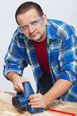 Man working wood with an electric planer — Stock Photo