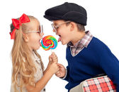 Kids sharing a large lollipop — Stock Photo