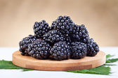 Blackberries on wooden plate — Stock Photo