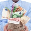 Stock Photo: Businessman hands with euro banknotes in a money bag
