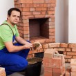 Stock Photo: Masonry worker building fireplace