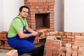 Masonry worker building fireplace — Stock Photo