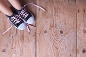 Child feet in sneekers on old wooden floor — Stock Photo