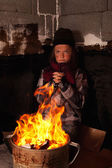 Poor beggar child warming up at the fire in a tin pot — Stock Photo