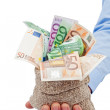 Businessman hand with a bag full of euro banknotes — Stock Photo