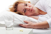 Taking pills - woman laying in bed — Stock Photo