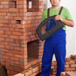 Mason building a traditional stove from bricks — Stock Photo