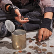 Beggar child counting coins sitting on damaged concrete floor — Stock Photo