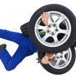 Mechanic covered by car tires — Stock Photo