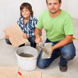 Father and son laying floor tiles together — Foto Stock