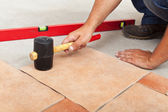 Installing ceramic flooring - fitting a tile — Stock Photo