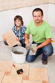 Father and son laying floor tiles together — Photo