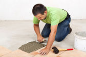 Man laying floor tiles - spreading the adhesive — Stock Photo