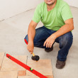Worker laying ceramic floor tiles — Stock Photo #34790051