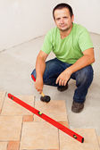 Worker laying ceramic floor tiles — Stock Photo