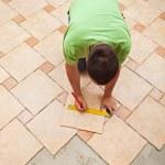 Man laying ceramic floor tiles — Foto Stock
