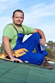 Worker laying bitumen roof shingles — Stock Photo