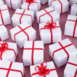Many christmas presents with red ribbons — Stock Photo