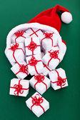 Spousta vánoční prezentovat, proudící z santa klobouk — Stock fotografie