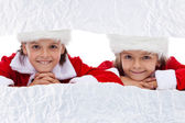 Kids watching the unwrapping christmas present — Stock Photo