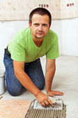Worker installing ceramic floor tiles — Stock Photo