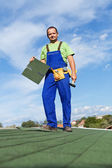 Worker installing bitumen roof shingles — Stock Photo