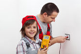 Happy boy helping his father mounting electrical wall fixtures — Stock Photo