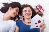 Happy young girls reading love letter — Stock Photo