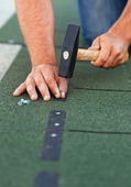 Worker installs bitumen roof shingles - closeup — Stock Photo
