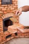 Masonry worker hands with brick and clay mortar on trowel — Stock Photo