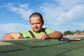 Installing the last strip of bitumen roof shingles — Stock Photo
