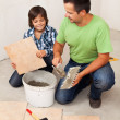 Man laying ceramic floor tiles helped by small boy — Stock Photo