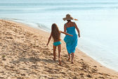 Woman and little girl on a morning walk by the sea — Stock Photo