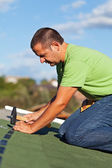Man on the roof fastening bitumen roof shingles — Stock Photo