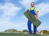 Worker putting bitumen shingles on a roof — Foto Stock