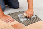 Worker hands spreading adhesive for ceramic floor tiles — Stock Photo