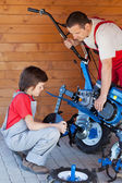 Boy helps his father mounting a cultivator machine — 图库照片