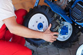 Man mounting tyre on a gasoline motor  tiller — Stock fotografie