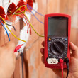 Electrician hands with multimeter and wires — Stock Photo #45811335