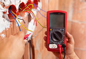 Electrician hands with multimeter and wires — Stock Photo