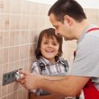 Boy assisting his father installing electical outlets — Stock Photo #45824015
