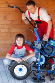 Man and boy servicing a cultivator machine — Stock Photo