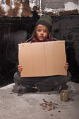 Poor beggar boy on the street with a cardboard sign — Stock Photo
