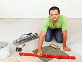 Man laying ceramic floor tiles on concrete floor — Stock Photo
