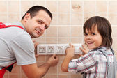 Father and son installing electrical wall fixtures — Stock Photo
